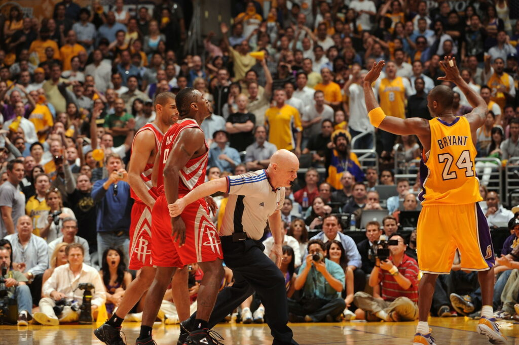 Ron Artest #96 of the Houston Rockets is restrained by Official Joe Crawford while Kobe Bryant #24 throws up his hands after an altercation in Game Two of the Western Conference Semifinals during the 2009 NBA Playoffs at Staples Center on May 6, 2009 in Los Angeles, California