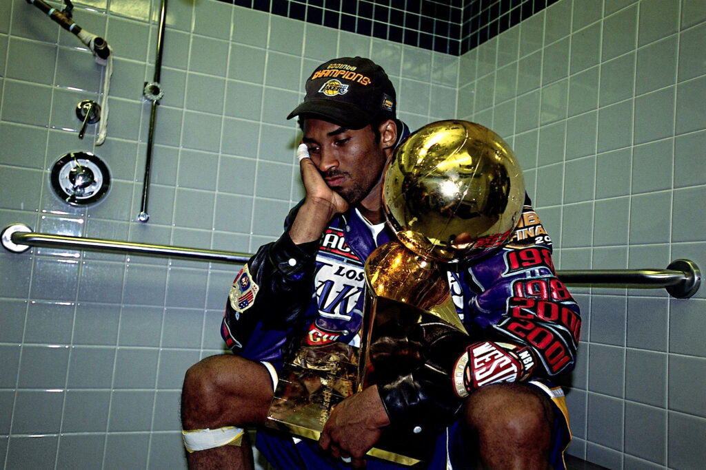 Kobe Bryant #8 of the Los Angeles Lakers poses with the NBA Championship trophy after defeating the Philadelphia 76ers in game five of the 2001 NBA Finals
